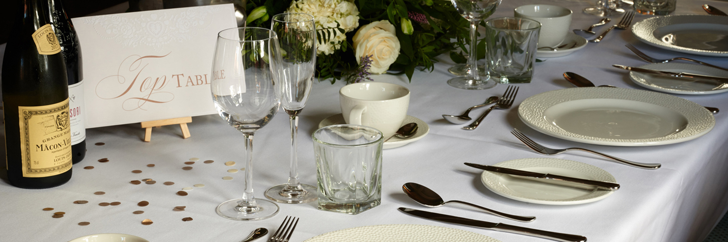 A wedding top table dressed with white table cloth, wine glasses and a place setting.